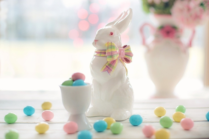 White porcelain bunny figurine with pink eyes and a bow next to a cup filled with small pastel Easter eggs with a pot of flowers in the background