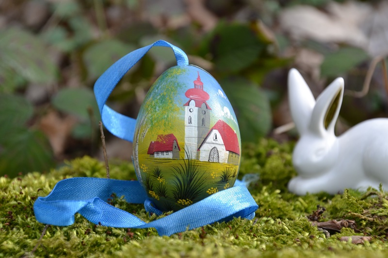 Painted Easter egg attached to a long blue ribbon upon green moss with green plants and a large eared white bunny figurine in the background