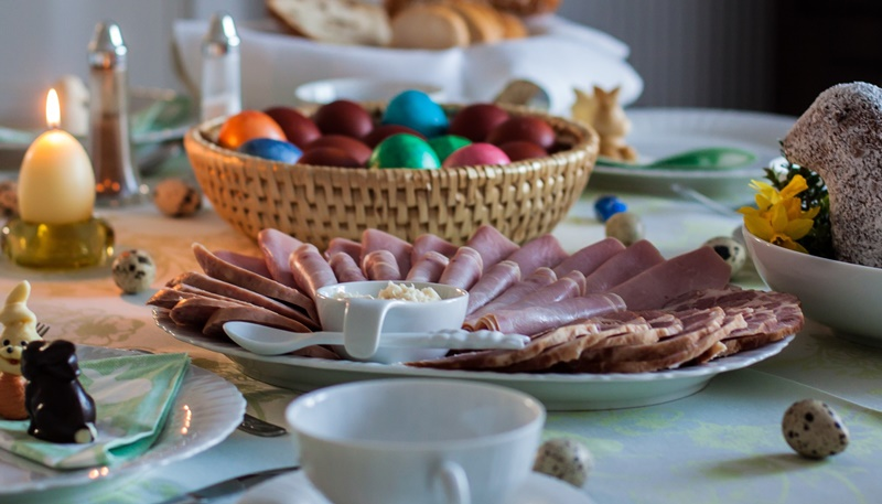 Sliced ham on a white plate on a table, next to a basket of colored Easter eggs, a lit egg shaped candle, a empty teacup in the foreground, and a basket of bread in the background, and small mostly uncolored speckled eggs placed about the table