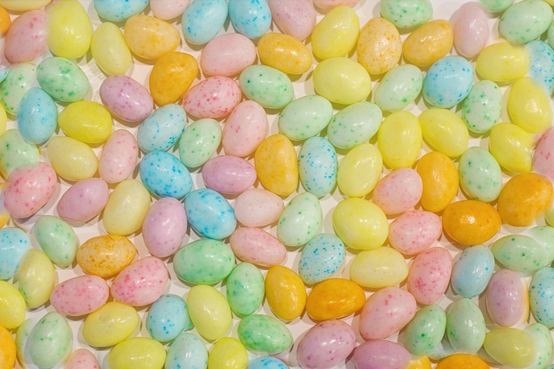 Numerous speckled pastel jelly beans laid out on a flat surface including yellow, blue, green, pink, orange, and purple beans for Easter J words
