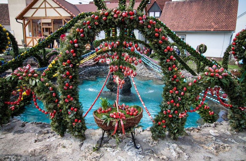 Easter well or Osterbrunnen with strings of colored eggs strung across a water fountain for Easter O words