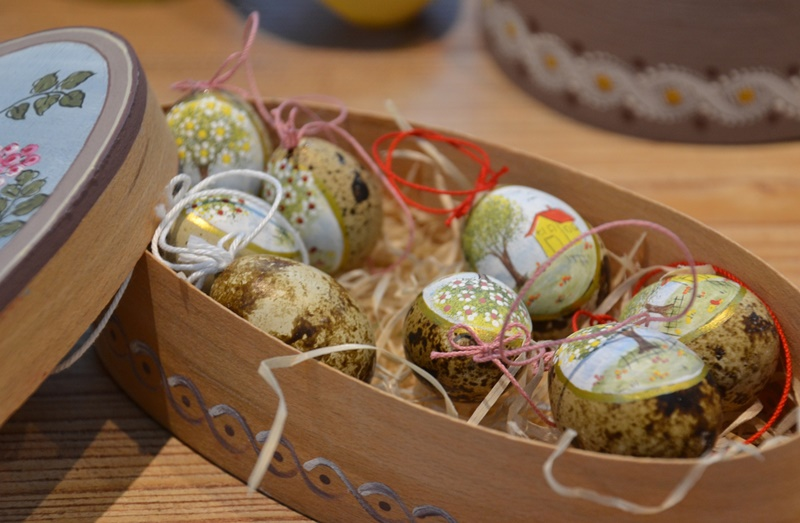 Eight traditional Easter painted quail eggs with colored string in a painted oval container made of thin brown wood for Q words