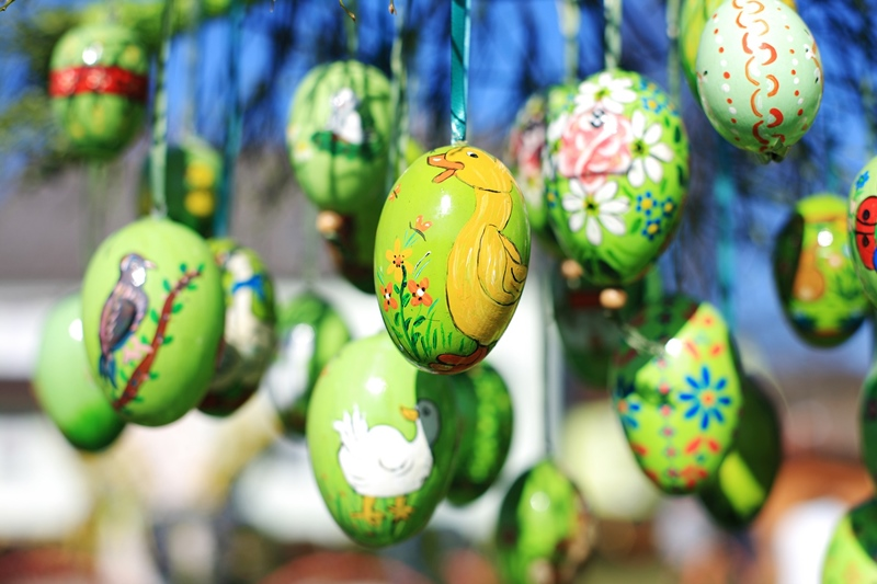 Green Easter eggs hung with ribbon with small paintings of ducks and flowers and birds on them