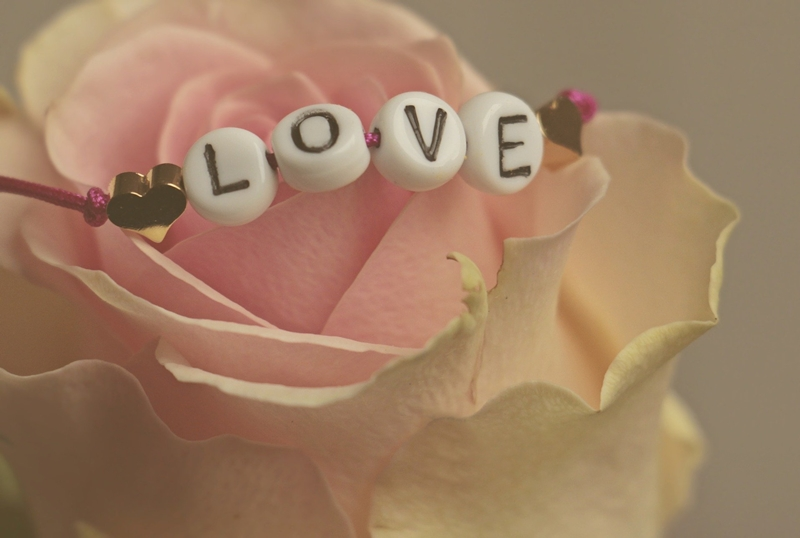 Letter beads l o v e on a pink and white rose with gold hearts and purple yarn too