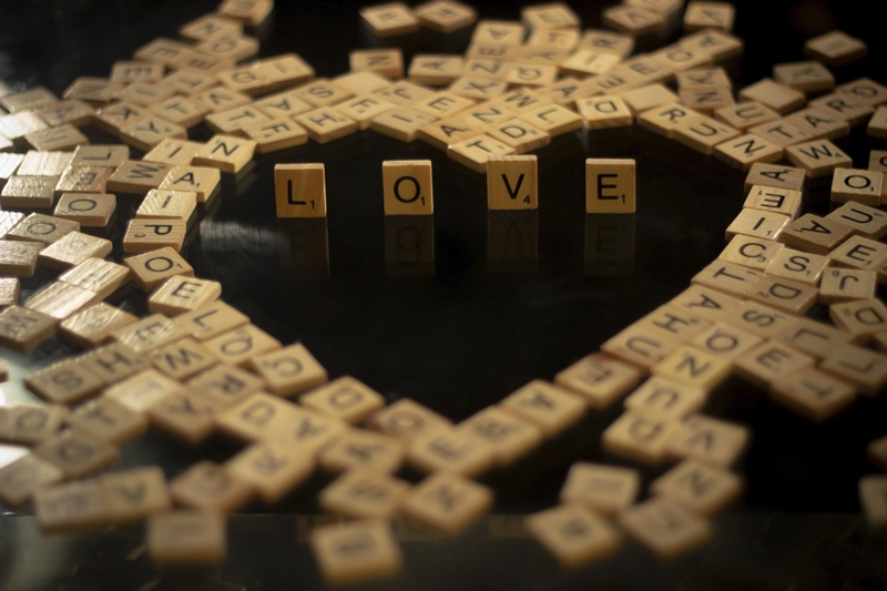 Letter tiles that spell the word love surrounded by other letter tiles in the shape of a heart